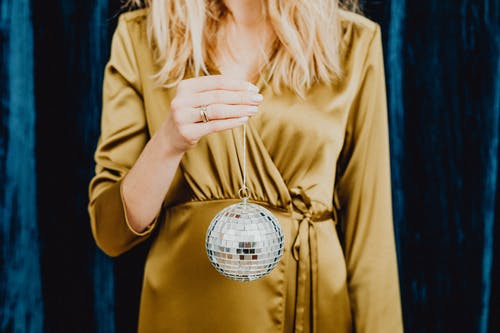 Woman in Golden Dress Holding Round Mirror Ball