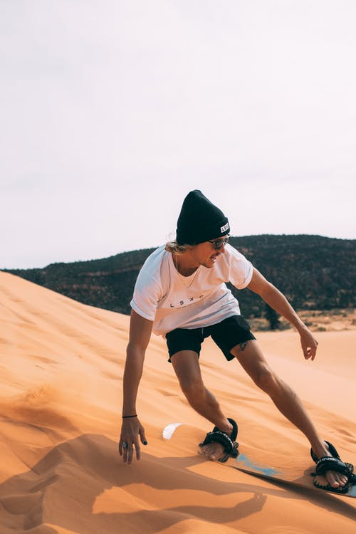 Woman in White T-shirt and Black Shorts Running on Brown Sand