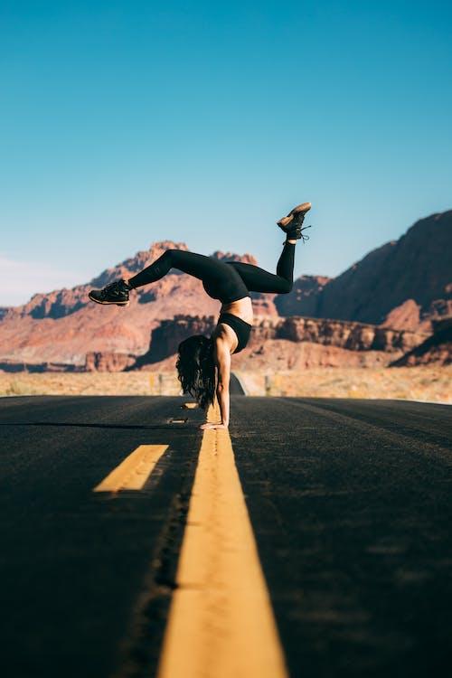 Man in Black Shirt and Black Pants Jumping on Gray Asphalt Road