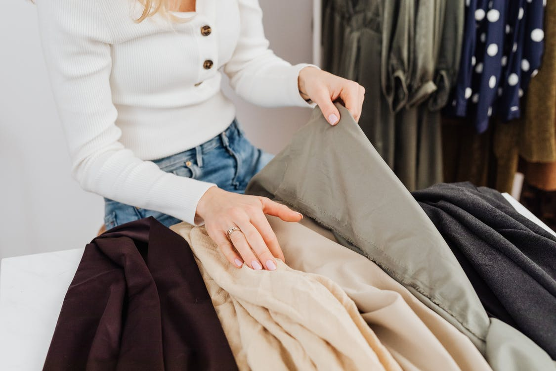 Woman in White Long Sleeve Shirt and Blue Denim Jeans Sitting on Bed