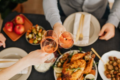 Food On The Table With Two People Having Wine