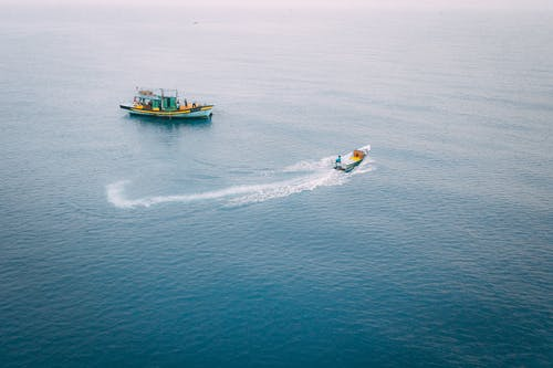 Drone view of vessels floating on rippling water of calm blue large sea