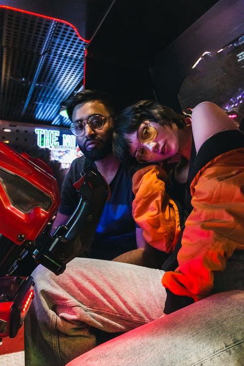 Man in Orange Jacket Beside Woman in Black Jacket