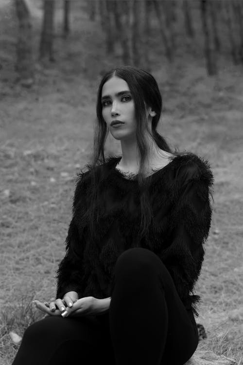 Black and white calm attractive female wearing fluffy dark sweater sitting on ground in woodland and looking at camera