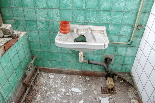 Demolished Lavatory with Rusty Pipes