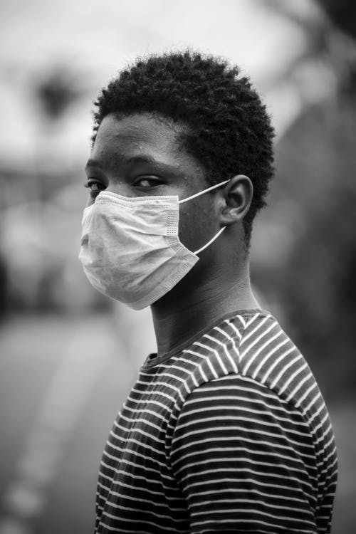 Grayscale Photo of Man in Stripe Shirt With Face Mask