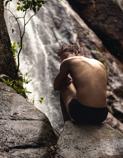 Woman in Black Bikini Bottom Climbing on Gray Rock