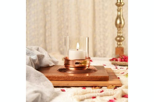 Close-Up Shot of a Lighted Candle on a Wooden Tray