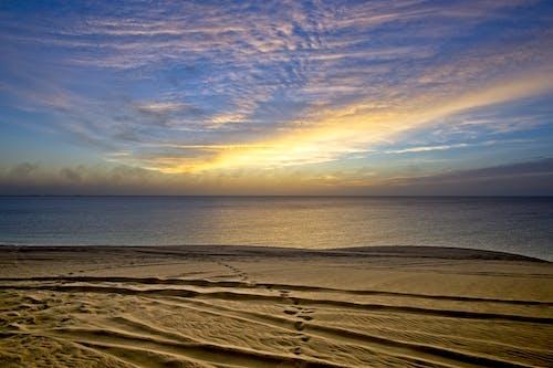 Picturesque view of sandy coast near rippling ocean under blue cloudy sky at sundown