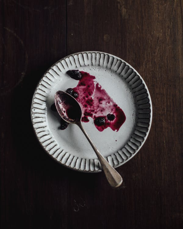 Top view of white empty plate with spoon and spread leftover blueberry sauce placed on wooden table in kitchen in morning