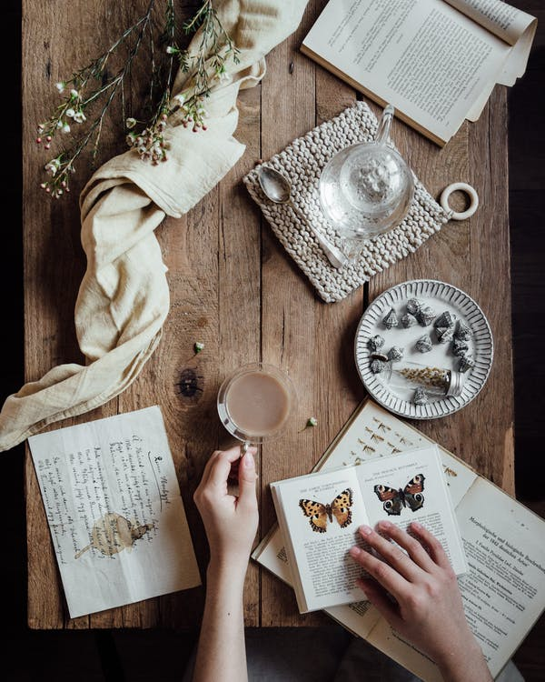 Person, Die Weißes Druckerpapier Auf Braunem Holztisch Hält