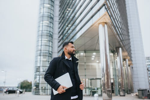 Dreamy unshaven ethnic male executive in stylish wear with netbook looking away against contemporary construction in city