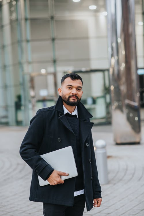 Young masculine bearded ethnic male office worker in trendy outfit with netbook looking at camera on city street
