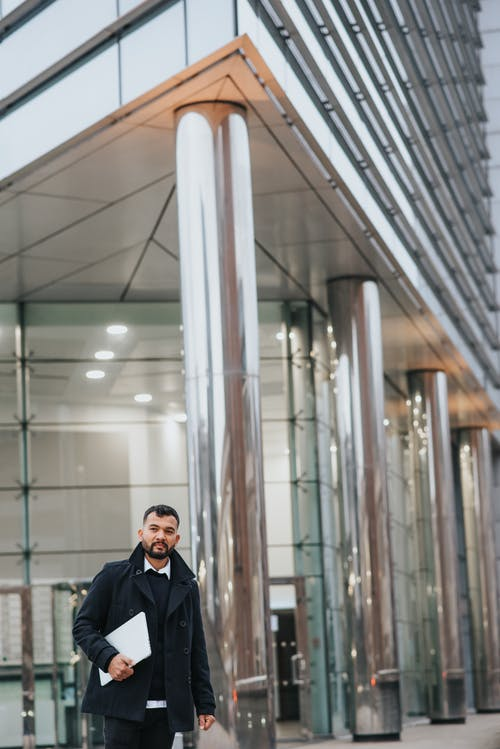 Pensive ethnic businessman with laptop near modern building in city
