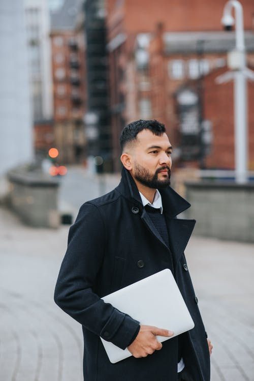 Young serious bearded ethnic male manager in trendy clothes with netbook looking forward on city street
