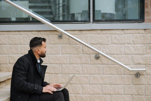 Pensive ethnic businessman with laptop on urban stairs