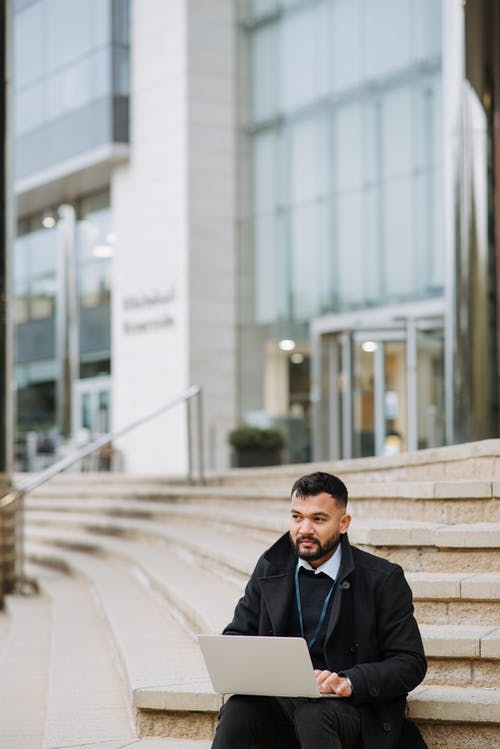 Pensive ethnic manager with laptop on urban stairs
