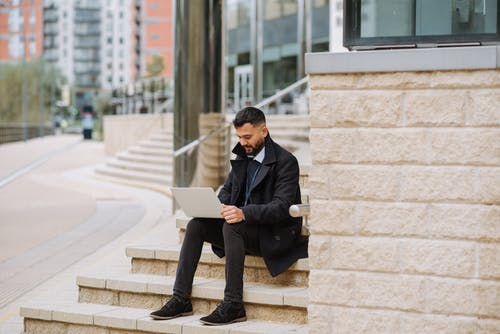 Serious ethnic manager working on laptop on urban stairs