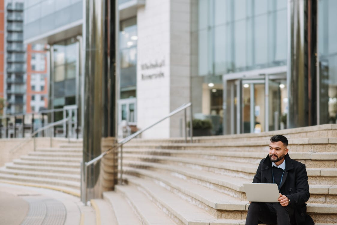 Thoughtful bearded ethnic male office worker with portable computer looking away on urban stairs against modern building