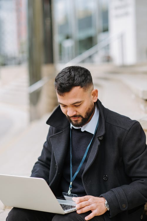 Attentive ethnic male manager watching laptop on urban stairs