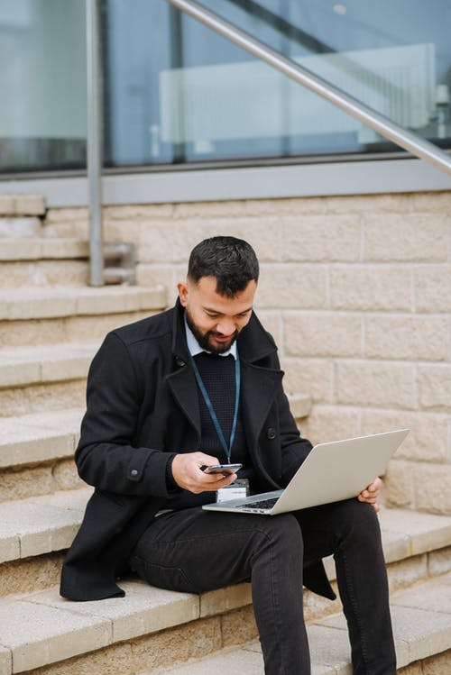 Attentive ethnic manager with laptop chatting on smartphone on staircase