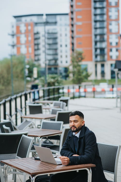 Pensive ethnic male executive with netbook looking away at table on veranda of urban cafeteria