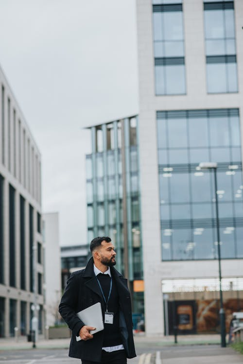 Trendy ethnic male office worker with badge and netbook looking away on road near urban contemporary constructions