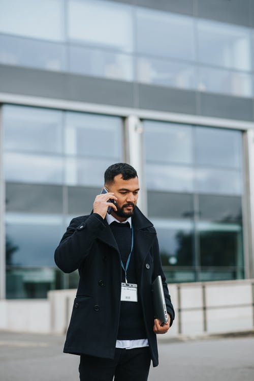 Ethnic manager with laptop talking on smartphone on urban street