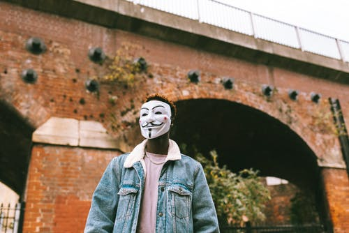 Anonymous black man in mask against urban arched bridge