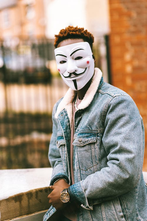 Faceless ethnic man in mask of anonymous on street