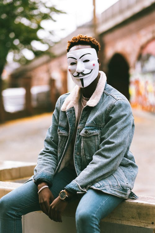 Anonymous African American male in denim wear and mask of anonymous sitting on urban bench
