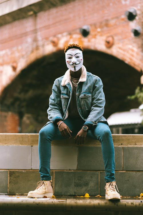 African American male in Anonymous mask and stylish clothes sitting on stone fence on street against brick construction in daytime