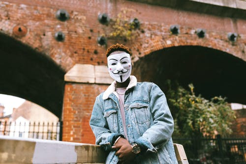 Black activist in Anonymous mask standing on street