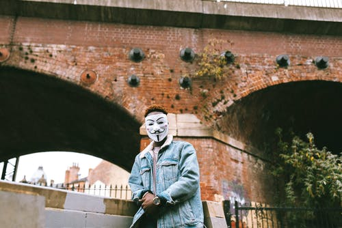 Black man in Anonymous mask standing against brick construction