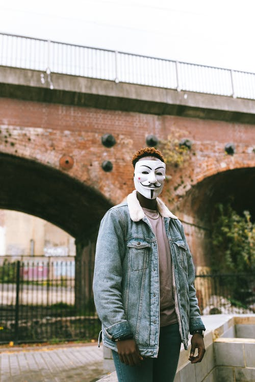 Black man in Anonymous mask standing and looking at camera