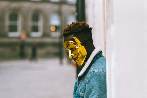 Side view of thoughtful African American activist wearing golden Anonymous mask as symbol of protest against current state policy standing near building on city street in daytime