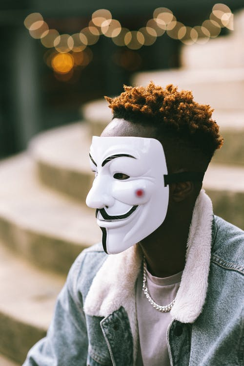 African American man in Anonymous mask sitting on stairs on street