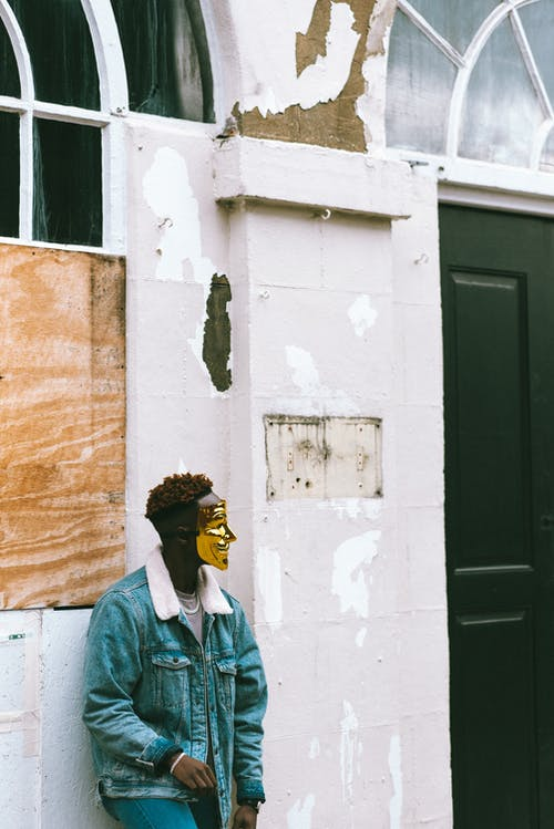 Black man in Anonymous mask standing near aged building on street
