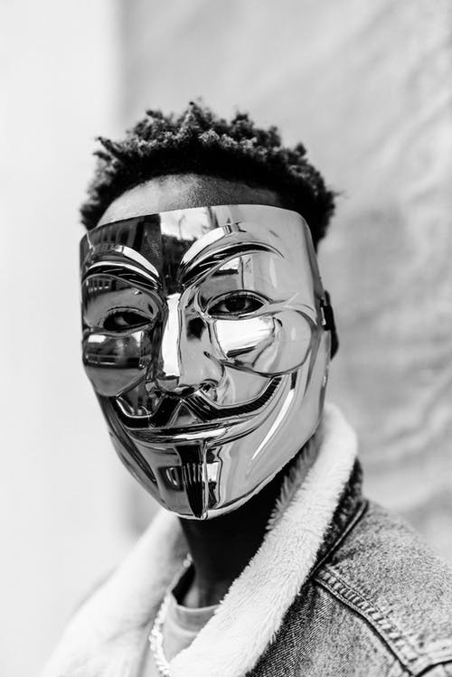 Black and white of unrecognizable African American activist wearing famous Anonymous mask as symbol of protest and looking at camera against blurred background