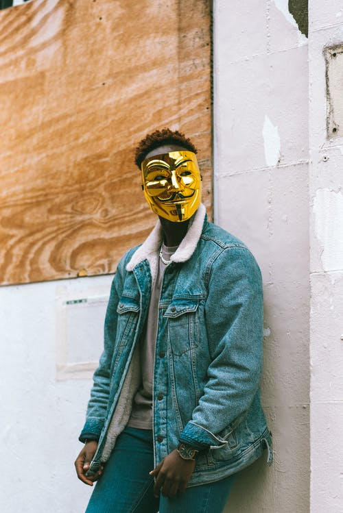 Black man in golden Anonymous mask leaning on wall and looking away