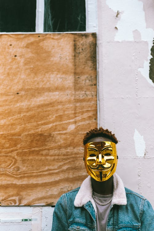 Black man wearing Anonymous mask as symbol of protest