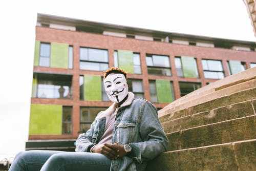 Black activist in famous Anonymous mask sitting on stairs against building
