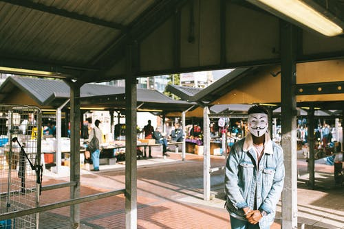 Unrecognizable black man in stylish clothes and Anonymous mask standing in local market in city and looking at camera in sunny day