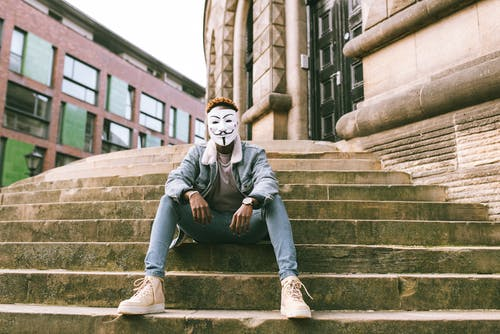 African American activist in white Anonymous mask and trendy clothes sitting on stone stairs on street against abandoned building in city in daytime