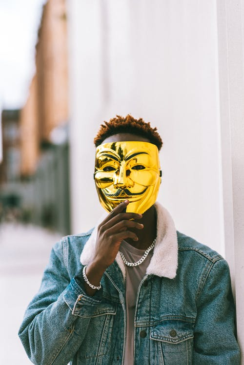 Black man covering face with Anonymous mask