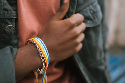 Crop black man showing bright fabric bracelet