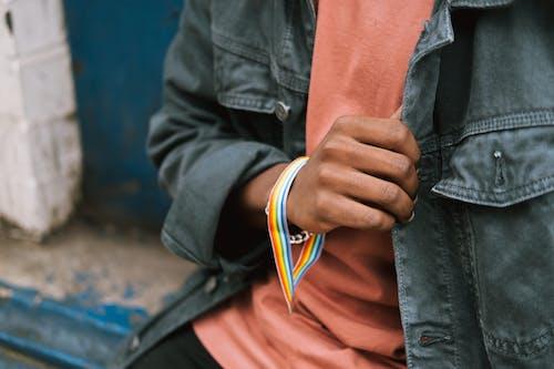Crop unrecognizable black man wearing gay bracelet on street