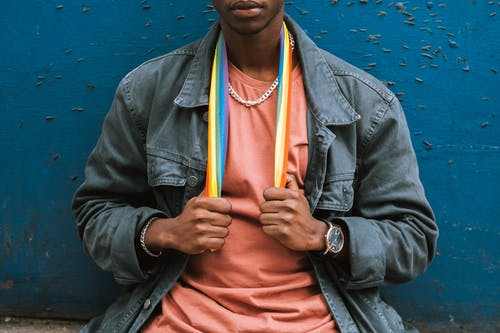Crop emotionless African American male in street style clothes wearing colorful LGBT flag on neck while sitting against shabby blue wall