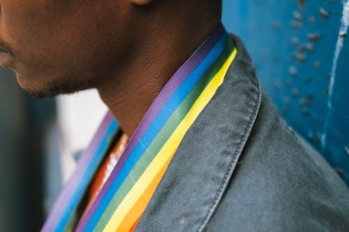 Crop faceless black man wearing LGBT flag on neck