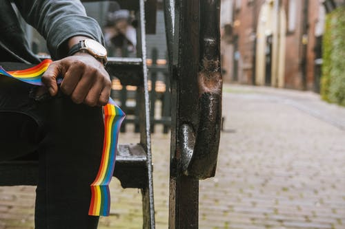 Crop anonymous African American male wearing casual clothes sitting on shabby stairs with LGBT ribbon on summer street